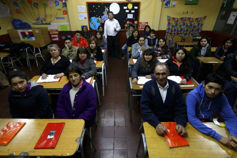 Teacher Guillermo Valenzuela with students of primary grade who are attending a night school for adults at Laura Vicuna school in Santiago, Chile. Ivan Alvarado - Reuters