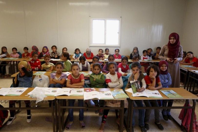 Teacher Hanan Anzi with Syrian refugee students at Al Zaatari refugee camp in the Jordanian city of Mafraq, near the border with Syria. Muhammad Hamed - Reuters