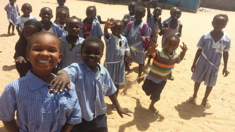 Young school children in The Gambia, West Africa, run towards the camera smiling