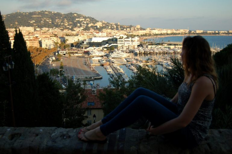 A girl looks over a beautiful view of Cannes harbour and town in the sunshine