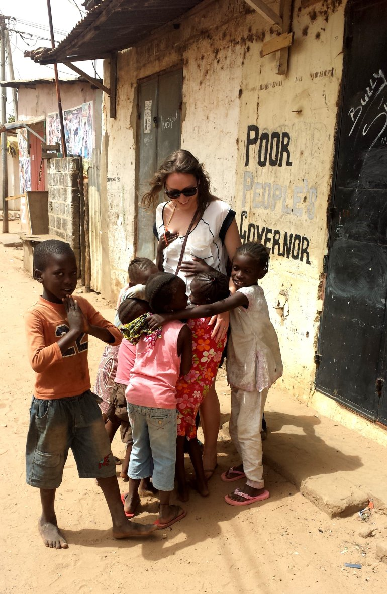 Local village children run towards and gather around a tourist in The Gambia, West Africa