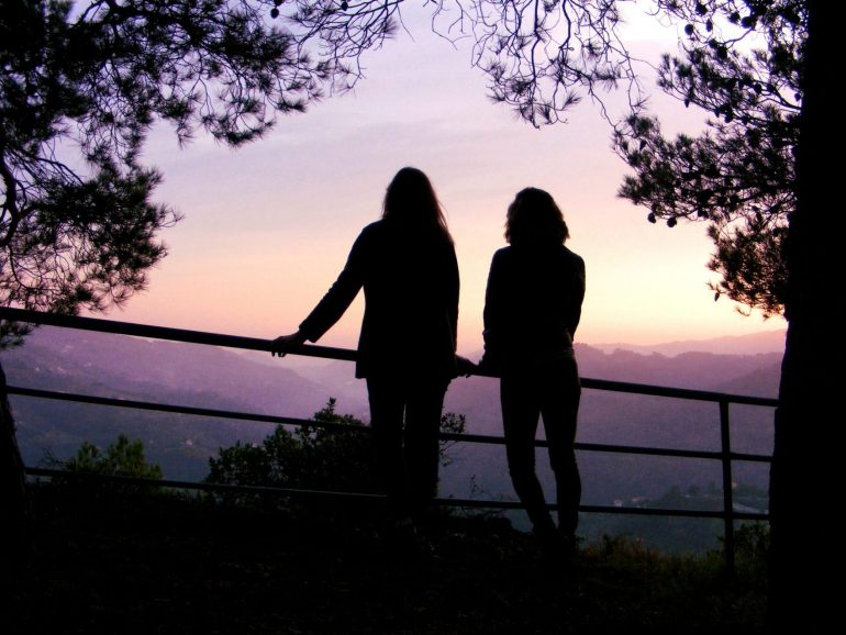 Two girls silhouetted against the sunset overlooking a valley in Northen Italy