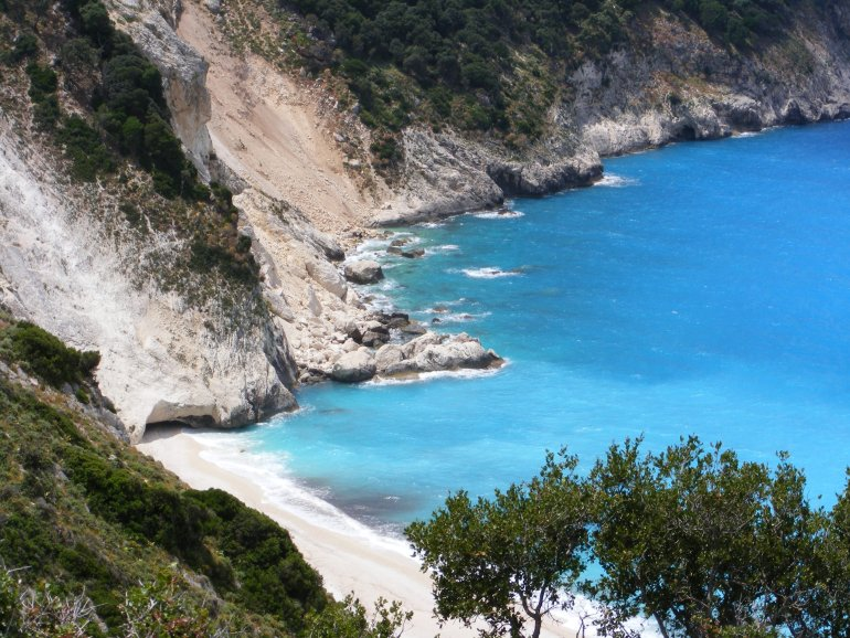 A view over rocks and cliffs tumbling into a bright turquoise sea at Myrtos Beach on the Greek island of Kefalonia