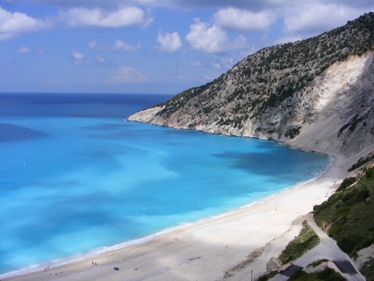 A beautiful view over Myrtos Beach, with white pebbles against a stunningly beautiful bright turquoise ocean in a bay surrounded by cliffs and green vegetation