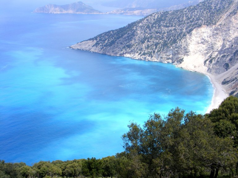 An insanely coloured ocean with vivid hues of turquoise and blue, surrounded by beautiful coastline in Kefalonia, Greece