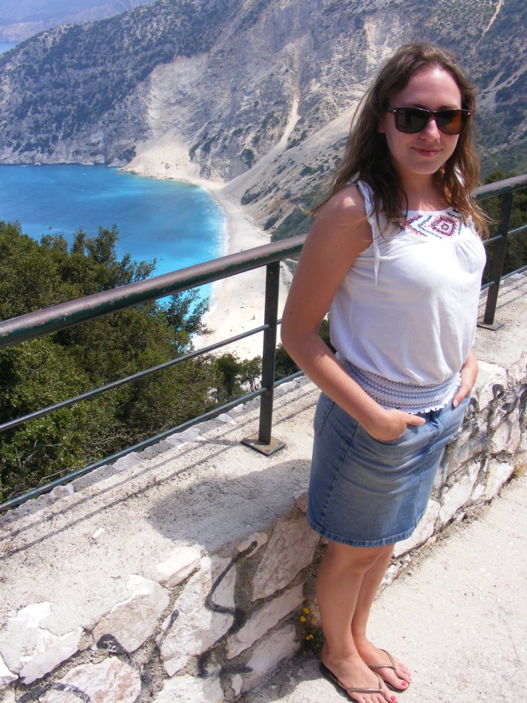 A girl wearing sunglasses and summer clothing smiles at the camera at a viewpoint overlooking a beautiful white sandy beach surrounded by cliffs in Greece