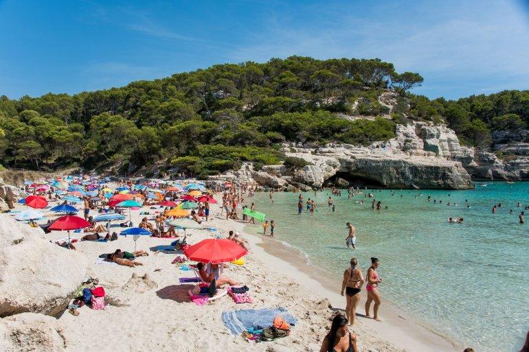 A busy beach at Cala Mitjana in Menorca, Spain