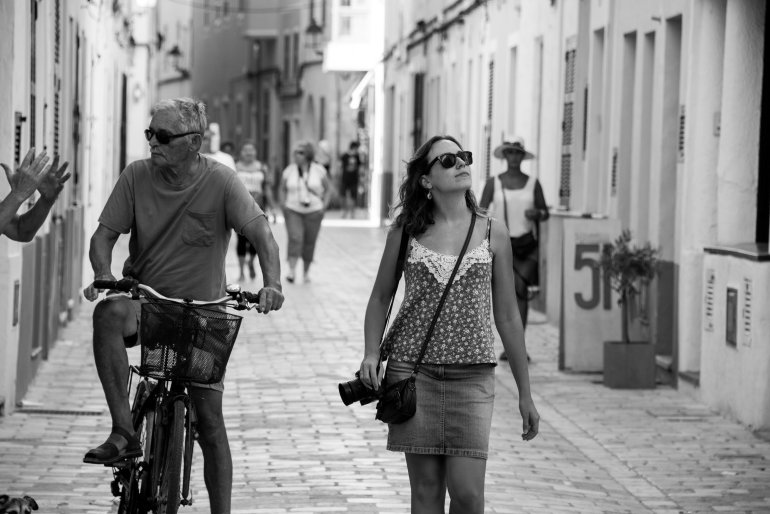 Girl wearing sunglasses and holding camera walks down rustic street on holiday