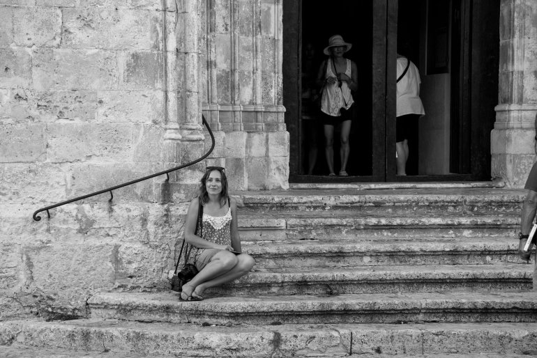 Girl sits on rustic steps of church in Menorca's Ciutadella