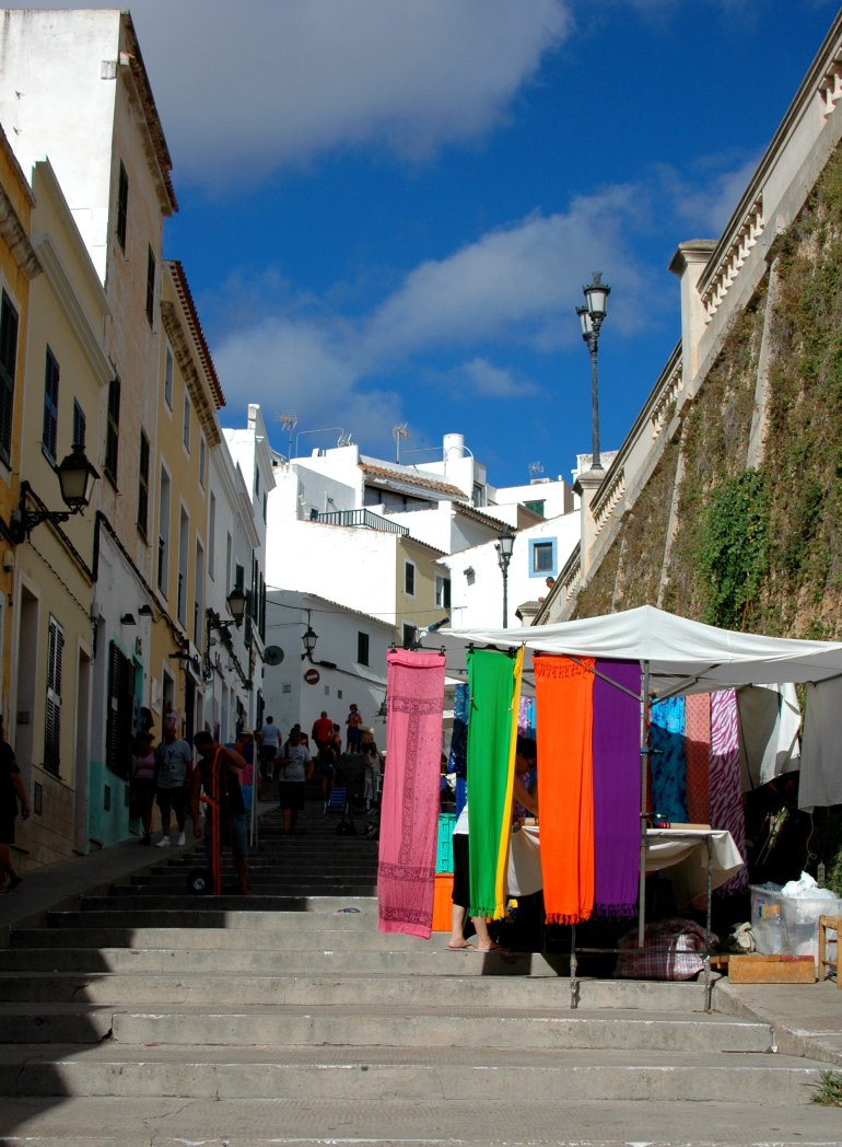 White-washed buildings and colourful blankets on a market stall in Spain