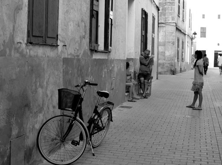 Bicycle with basket leans against wall in front of locals talking in street in Spain
