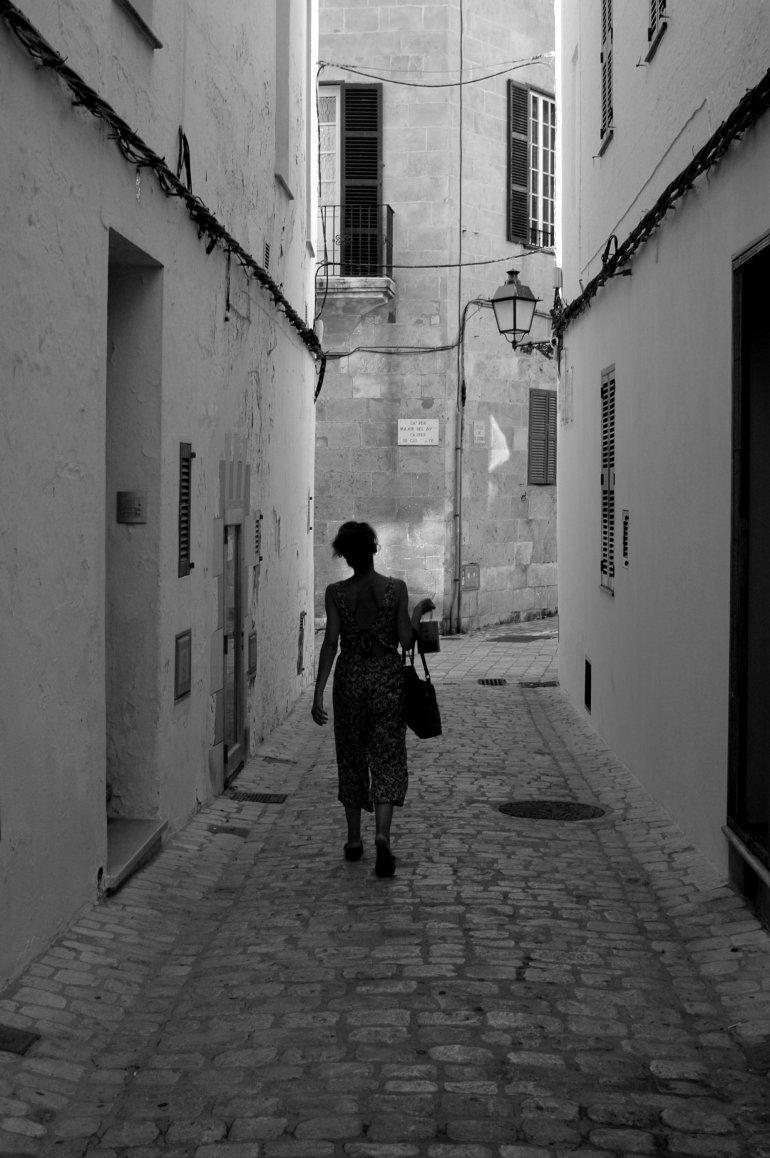 Silhouette of woman strolling down rustic street in Ciutadella Menorca