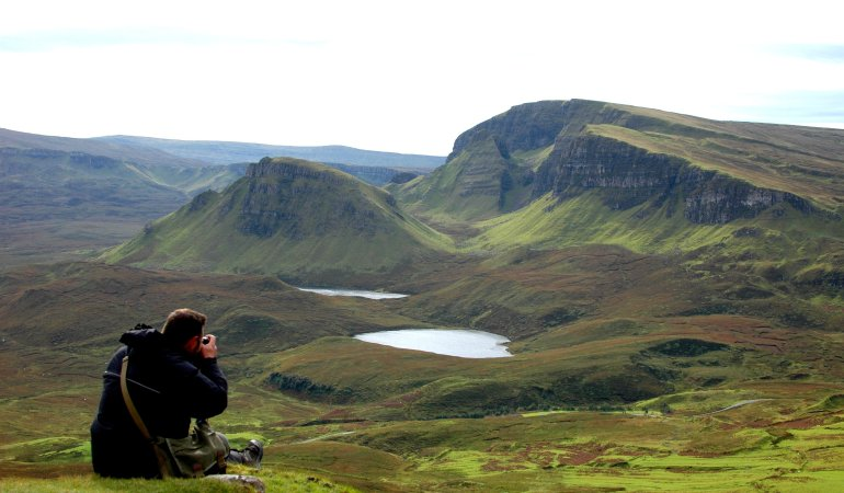 Man takes photograph of beautiful mountain scenery at the Quiraing on the Isle of Skye in Scotland