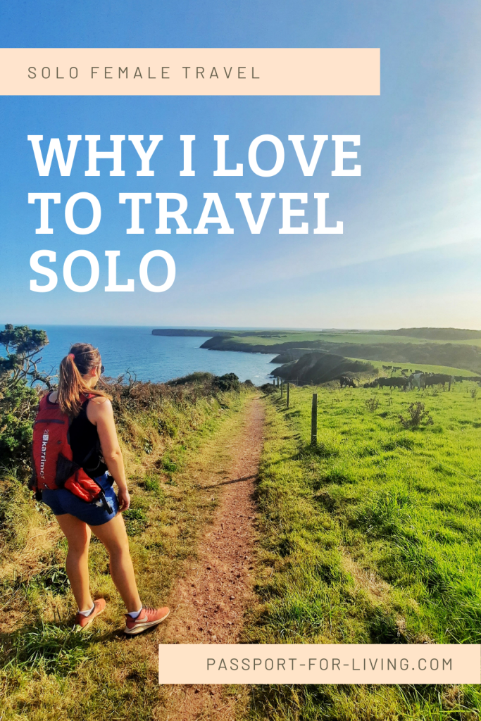 Why I love to travel solo - girl looks out on a coastal path in wales