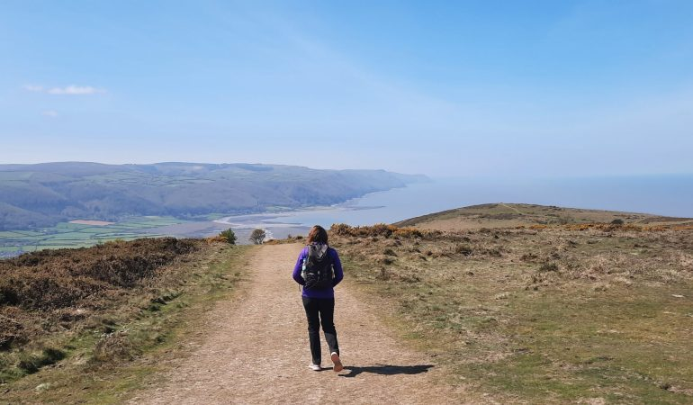 Hiker looks out over beautiful coastal scenery on the South West Coast Path from Minehead to Porlock Weir