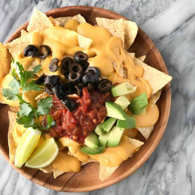 Protein-Packed Vegan Cheese Sauce | Plate of nachos with vegan cheese sauce | Whole foods plant based | Oil-free | #plantbased #vegan #oilfree #wfbp | https://passtheplants.com/