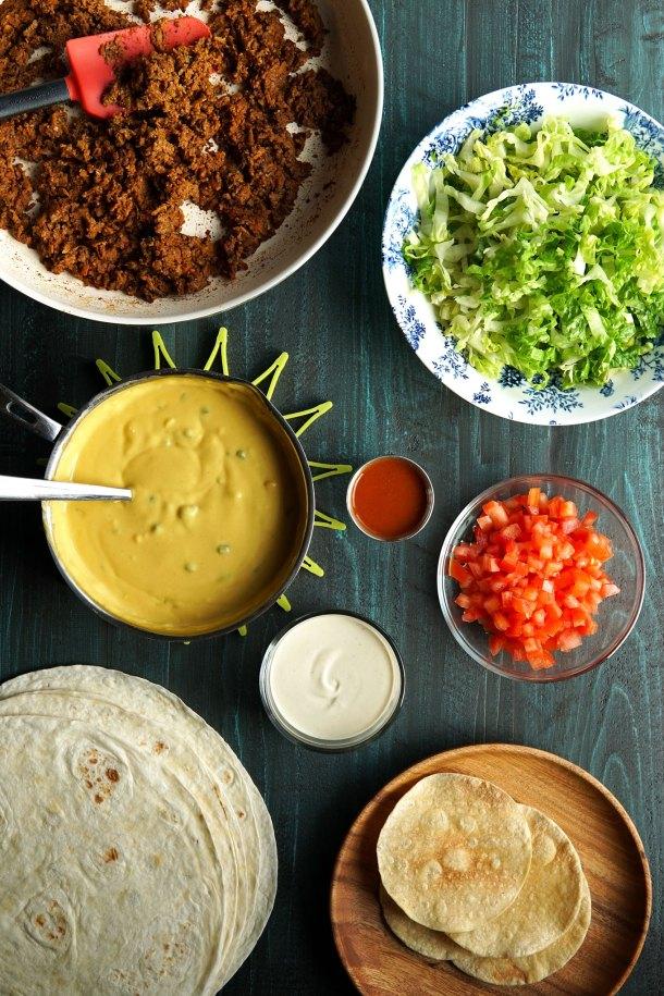 Overhead image of ingredients for vegan crunchwrap supreme | Vegan taco meat, vegan queso, vegan cashew cream, lettuce, tomato, flour tortillas, corn tortillas, hot sauce
