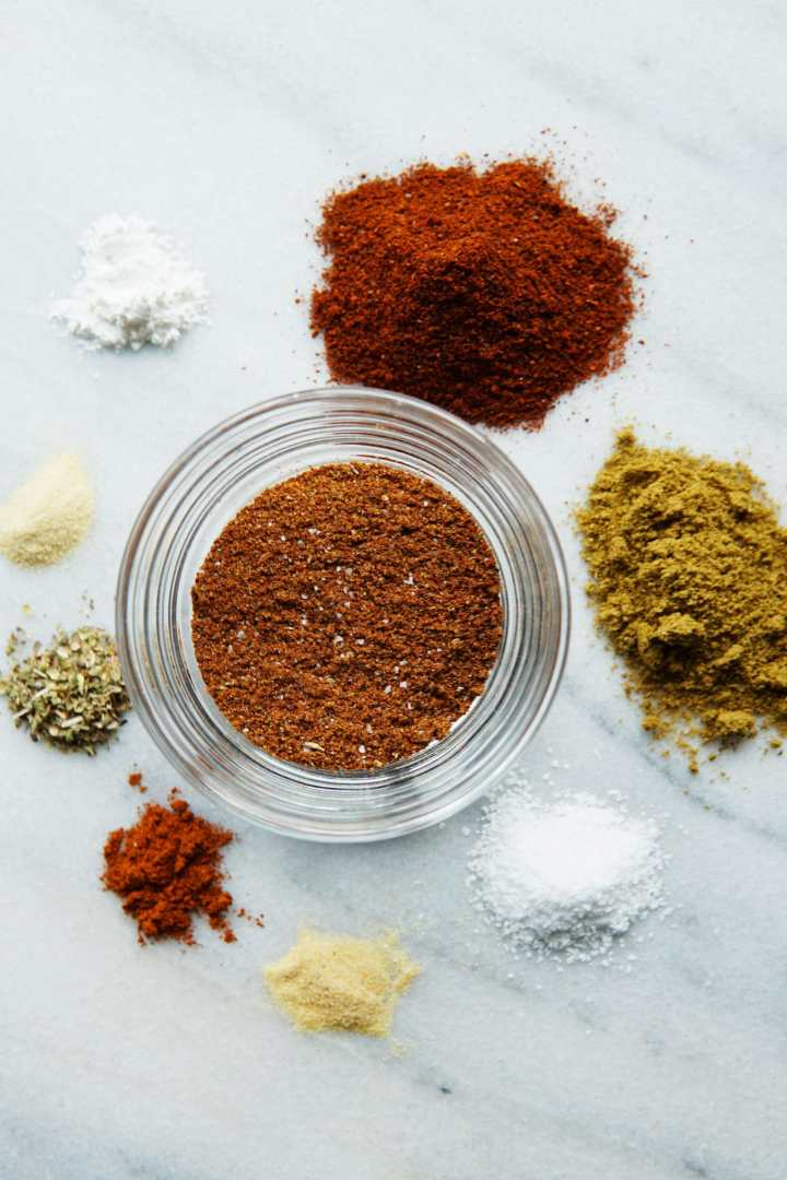 spices for taco seasoning mix in a bowl and displayed on a counter - chili powder, ground cumin, salt, onion powder, garlic powder, paprika, oregano, cornstarch