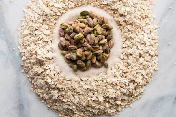 circular overhead shot of rolled oats, sugar, and pistachios