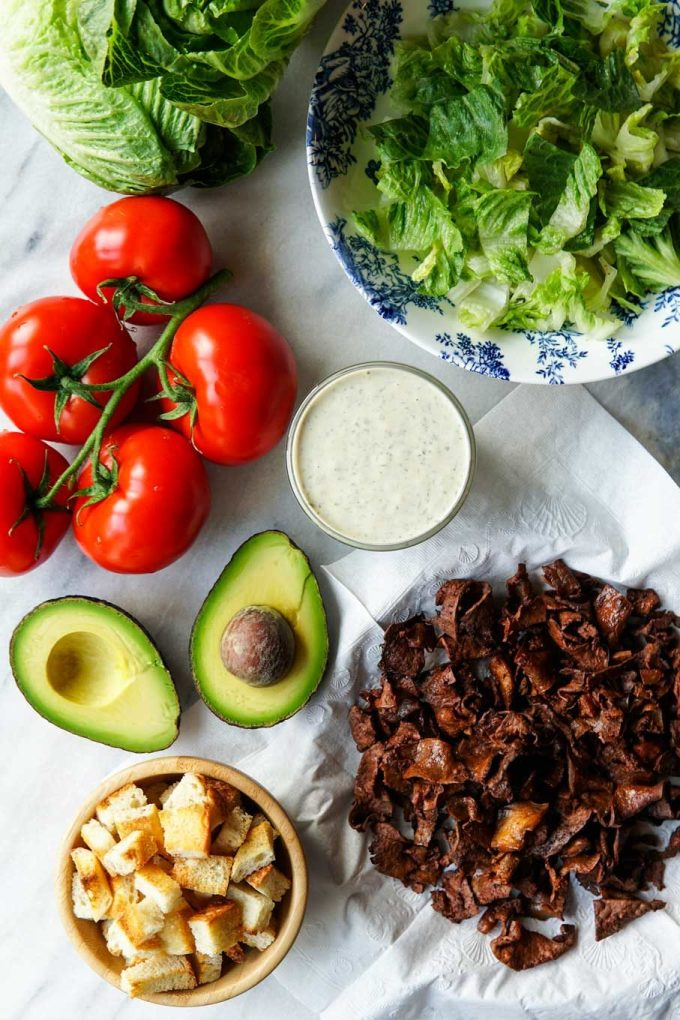 overhead image of ingredients for Vegan BLT Salad - tofu bacon, croutons, avocado, vegan ranch dressing, tomatoes, romaine lettuce