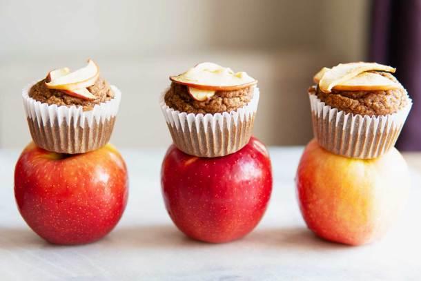 apple cinnamon blender muffins sitting atop three apples