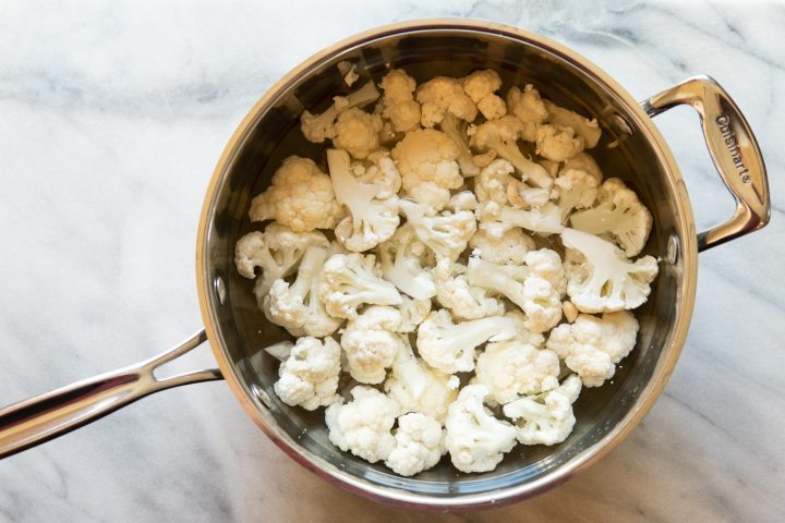 cauliflower, garlic, and raw cashews in a pan of water ready to be cooked