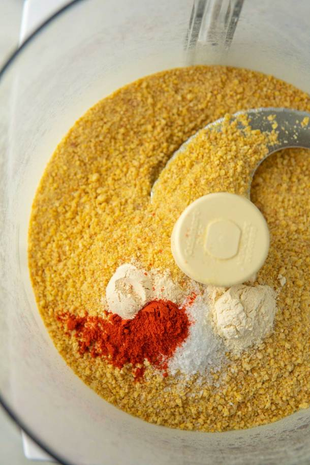 Breadcrumbs made from chickpeas in food processor bowl with paprika, garlic powder, salt, and onion powder