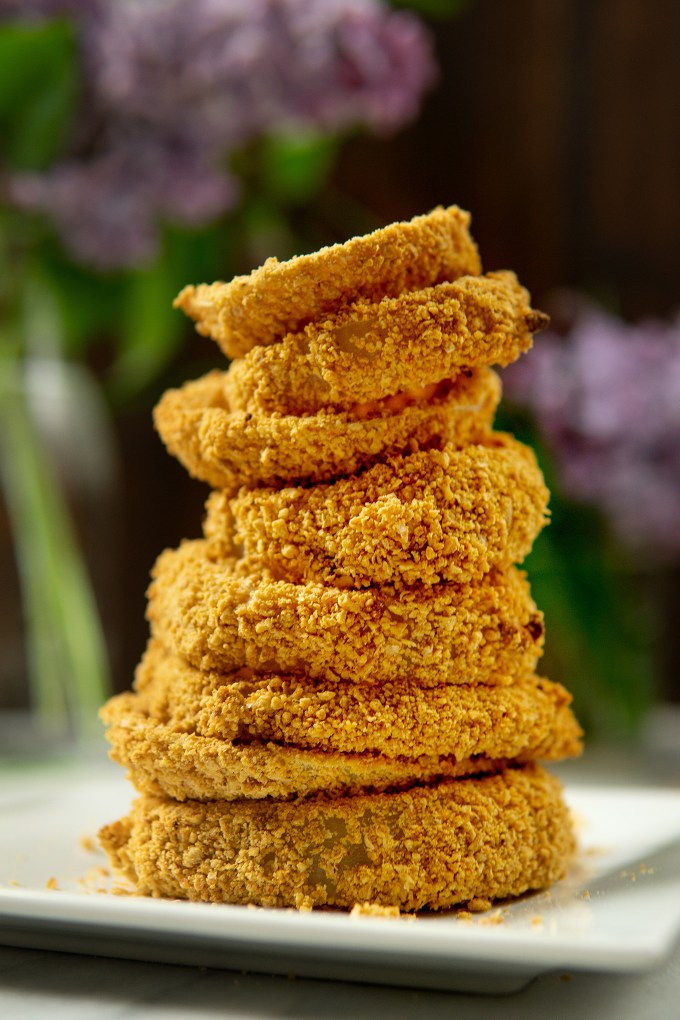 vegan baked onion rings stacked on a plate