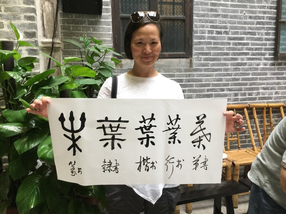 Photo of Linda Yip holding a calligraphic scroll of the Yip family name in various styles.