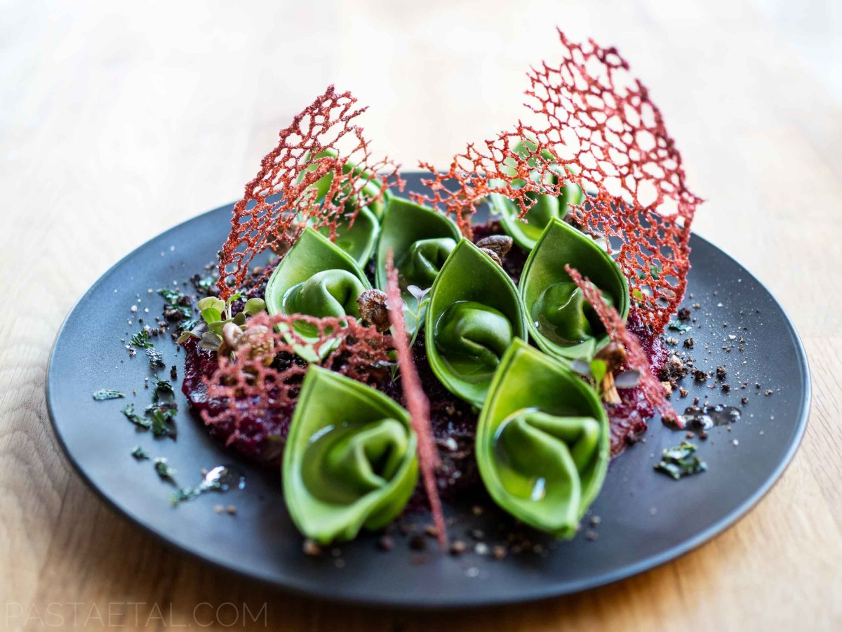 landscape green nettle cappellacci pasta on a beetroot puree with rhubarb and cocoa crumb and carrot tuile on a plate