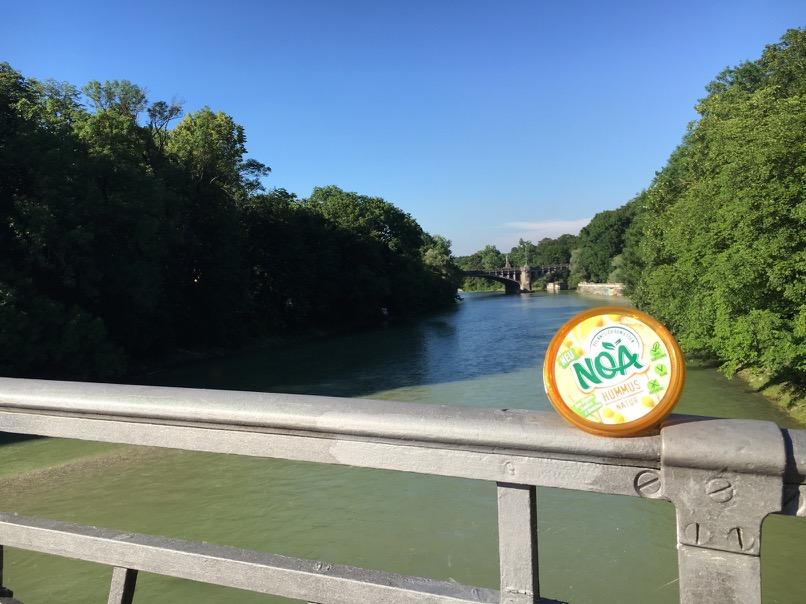 Pastamaniac: Artikel bei Mucbook über das Bloggerevent anlässlich der Markteinführung von NOA. Blick von der Brücke auf die Isar mit Noa-Verpackung auf dem Geländer.