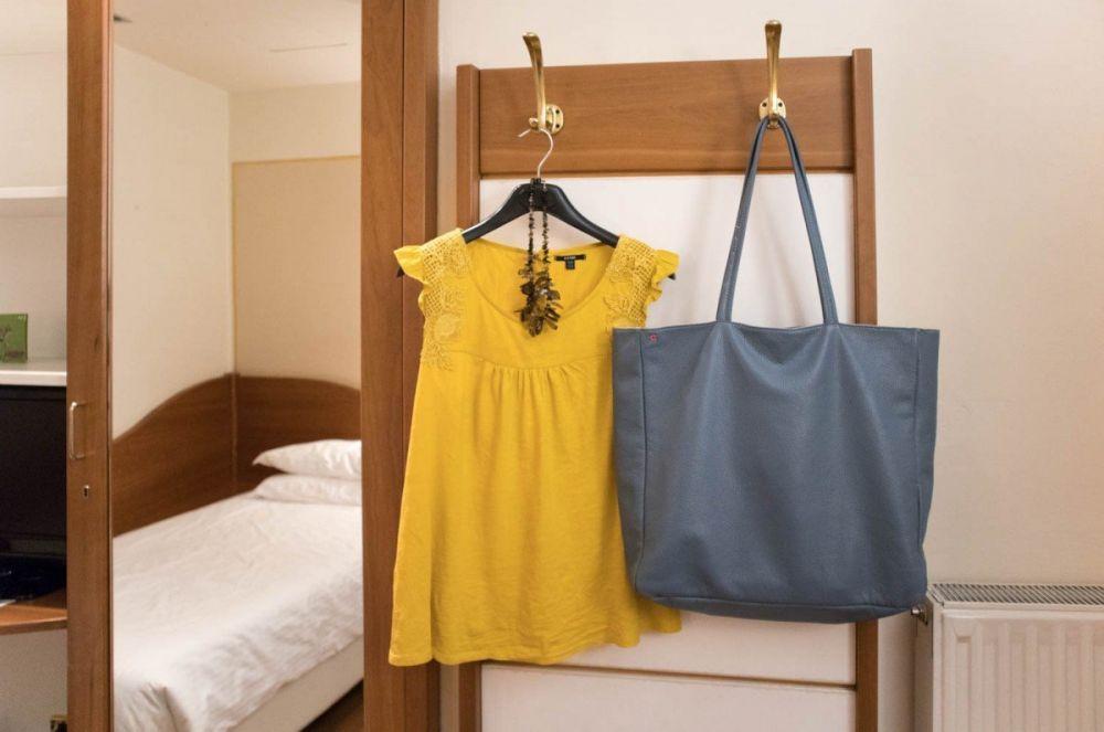 Vestiti e borsa appesi nella mia camera all'Hotel America di Trento
