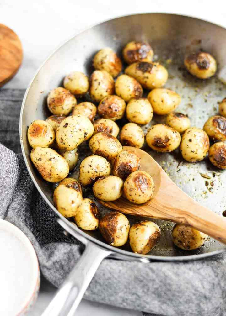 potatoes roasting in a pan with spoon and herbs