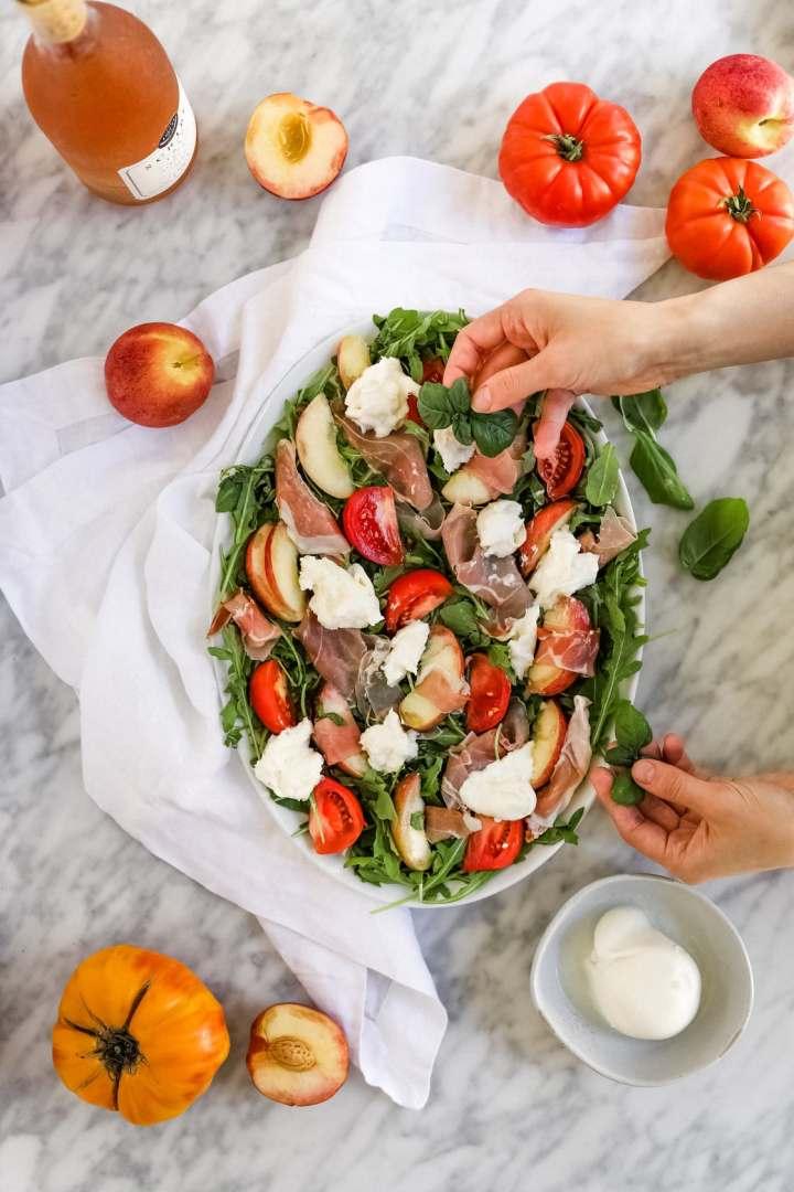 putting basil on prosciutto burrata salad