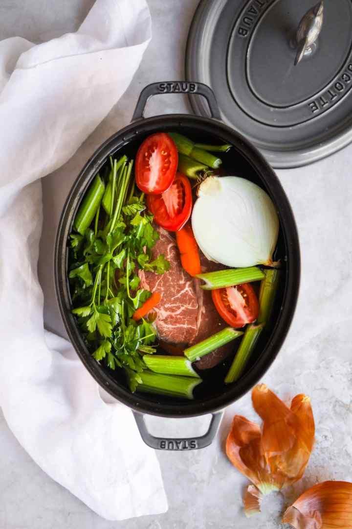 Italian beef soup ingredients in graphite Staub dutch oven