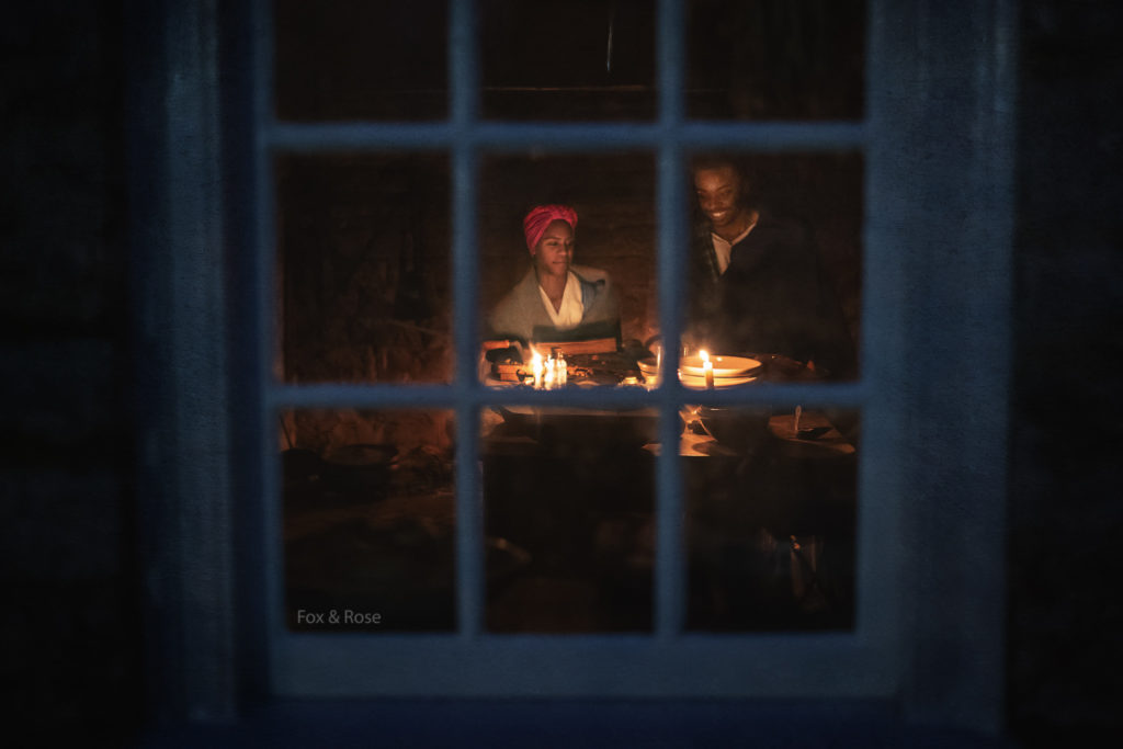 Two actors portraying enslaved workers through a window