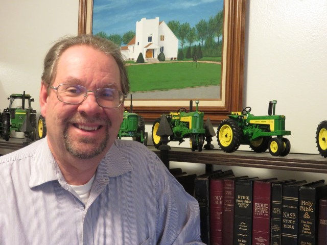 Pastor Phil in his office with John Deere Tractor models