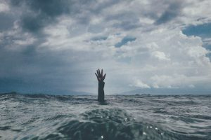 An arm and open hand reaching up out of choppy waters.  Backdrop of a stormy sky.