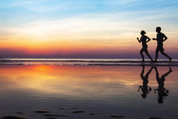 two runners on the beach, silhouette of people jogging at sunset, healthy lifestyle background