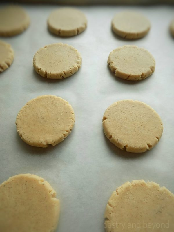 Steps of making Easy Cinnamon Cookies: Cookie dough balls that are flattened with a measuring cup