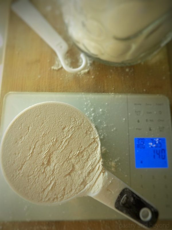Flour in a measuring cup on a digital food scale.