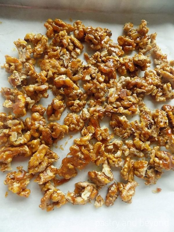 Caramelized walnut pieces on a parchment paper.