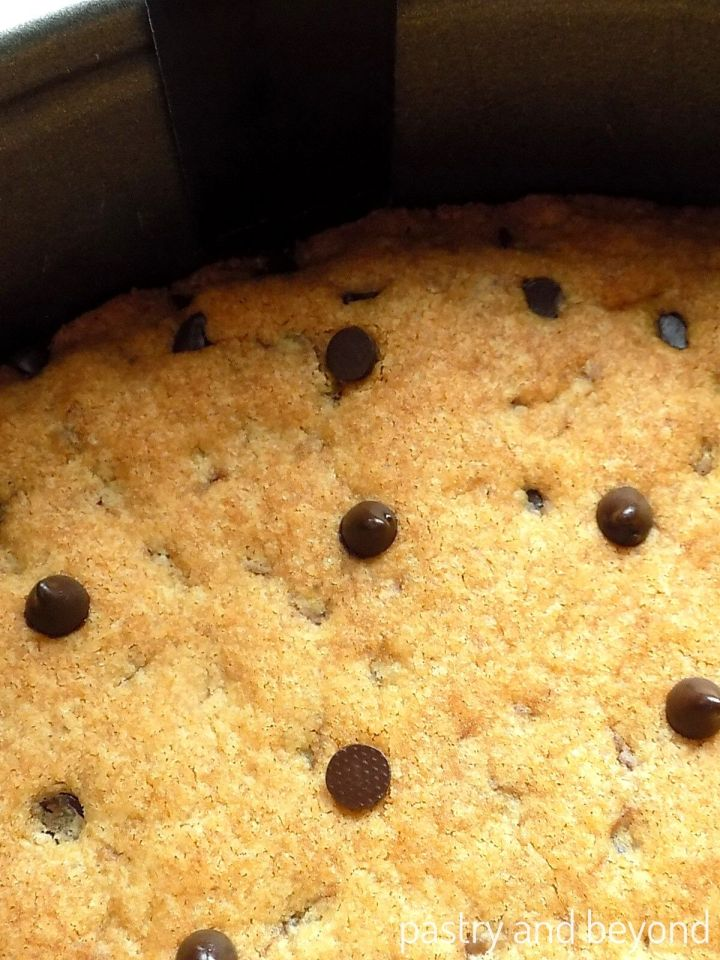 Loosening the cookie cake from the pan with a thin, small spatula
