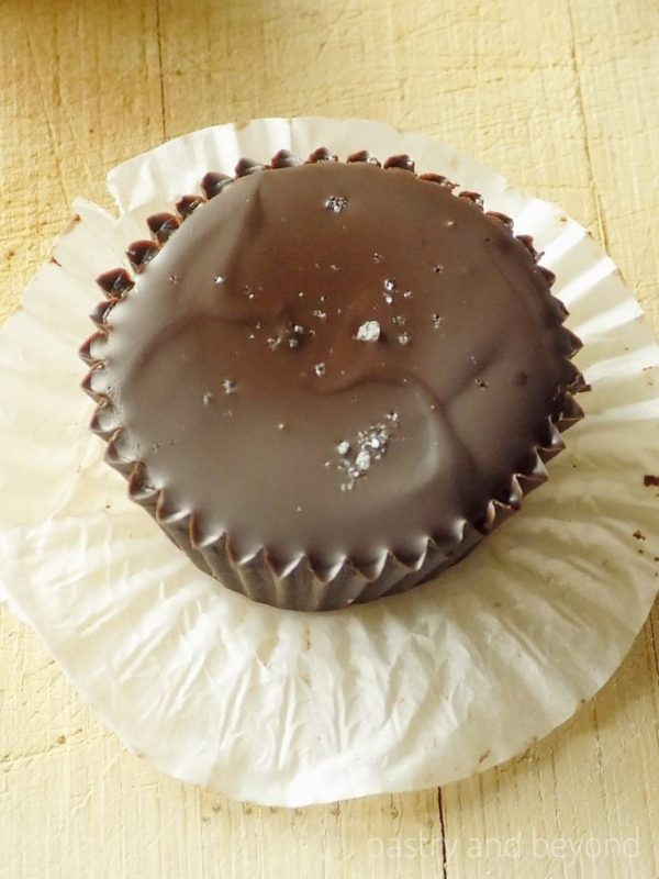 Caramel chocolate cup with sea salt on a white cupcake liner.