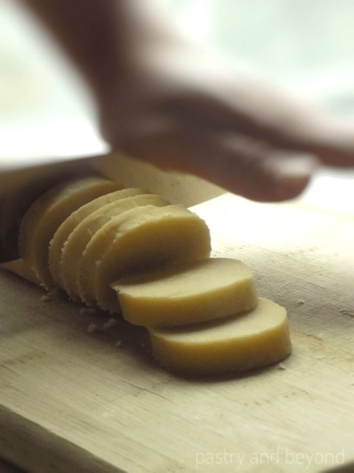 Slicing the dough on a wooden cutting board.