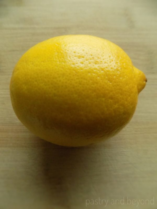 Lemon on a wooden chopping board.