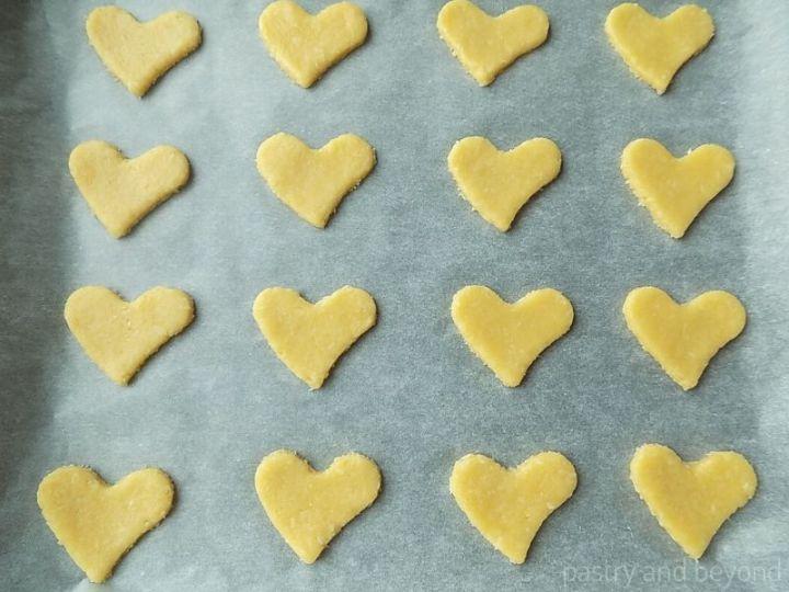 Cut out heart cookie dough on a baking sheet.