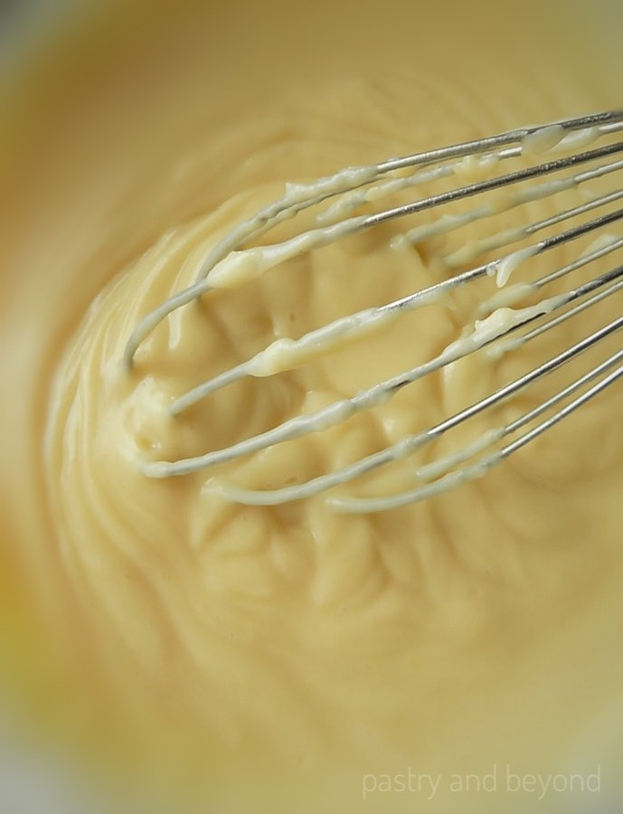 Pastry cream in a bowl with a whisk.