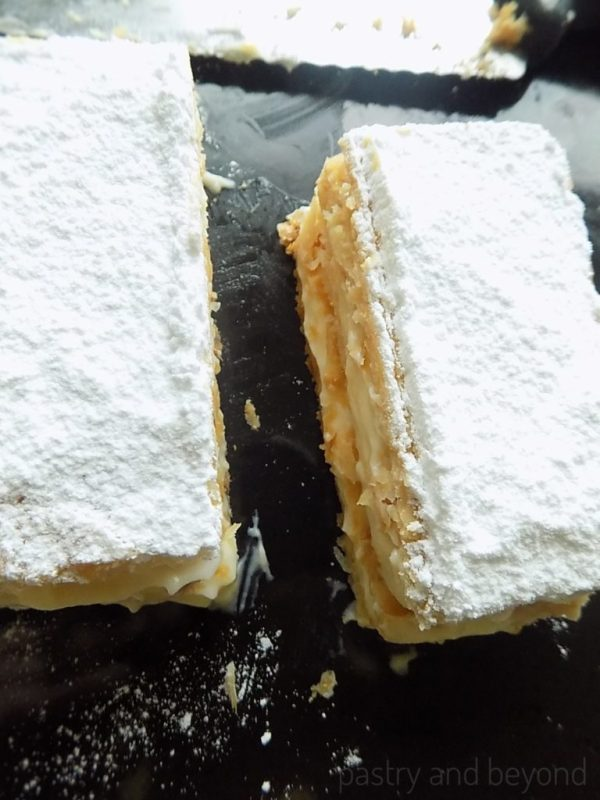 Mille-Feuille slice on a black surface.