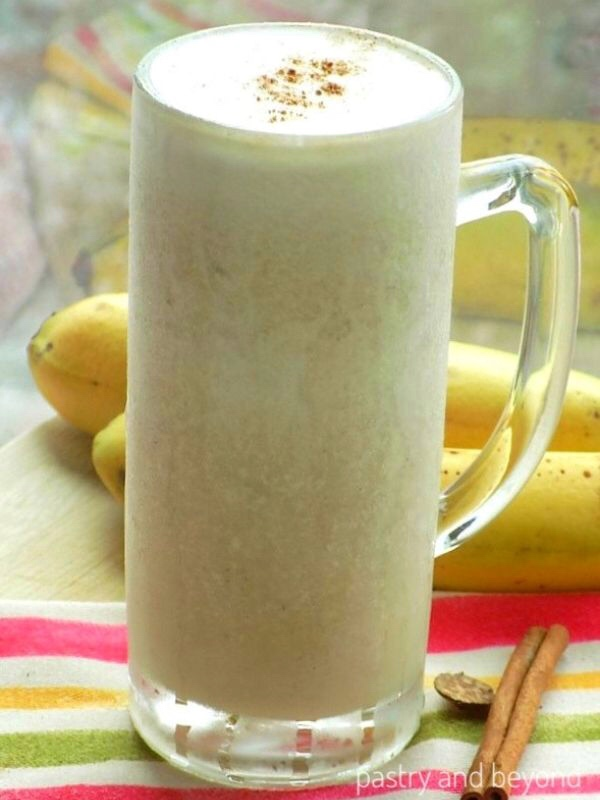 Healthy banana smoothie and bananas in the background.